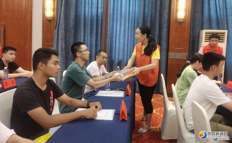 志愿者为受助学生发放助学书籍